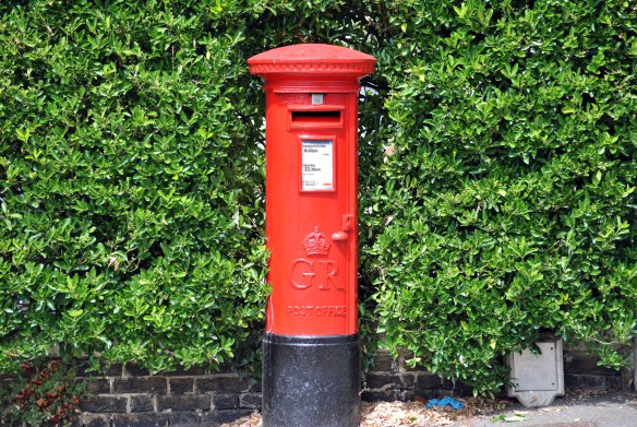 A postal box back amongst a hedge. The G.R. is for George Regina – King George VI, predecessor to Queen Elizabeth II. …….. The white area is the collection times. Mon-Fri – 6.00pm Saturday 11.30am. Silver square at the top is the day of the next collection, in this case – TUE